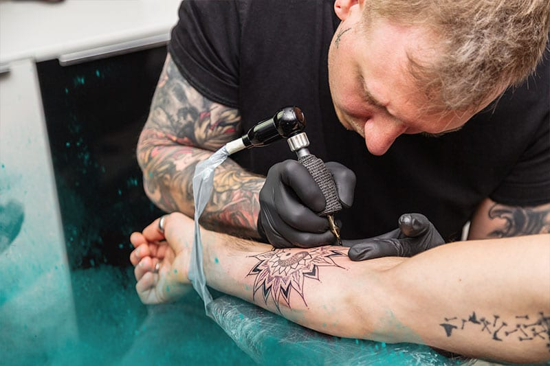 tattoo artist doing an arm tattoo